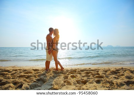 Young couple relaxing on a tropical beach at sunset