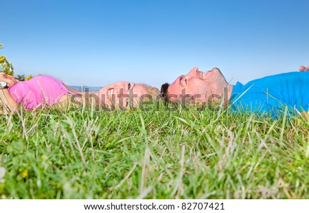Young couple relaxing on grass in park against blue sky