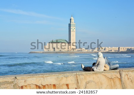 Young couple relaxing on seafront with view of Mosque of Hassan II in Casablanca, Morocco