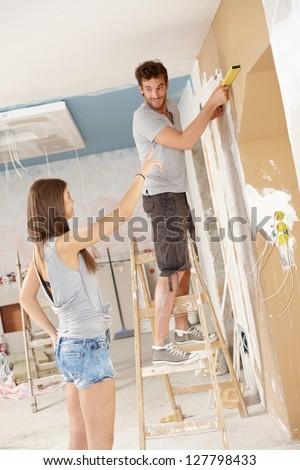 Young couple renovating home, DIY, measuring.