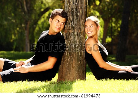 Young couple resting in the park near the tree - stock photo