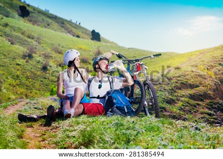 Young couple resting together on nature with the bike in the mountains. Youth sports. Man drinks water from a bottle.