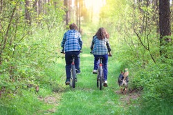 Young couple ride bicycles in the forest back to camera. Dog walking nearby