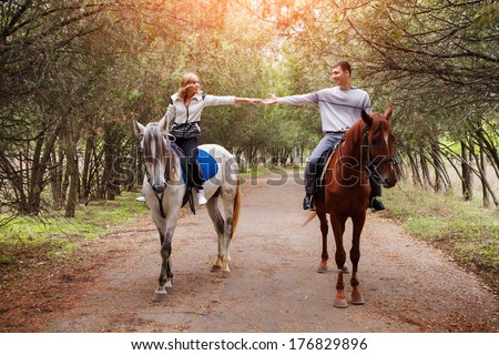 Young couple riding a brown horse at countryside at summer