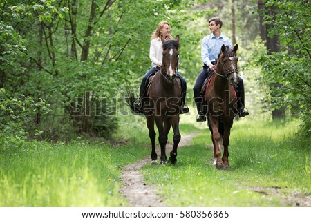 Young couple riding horses.