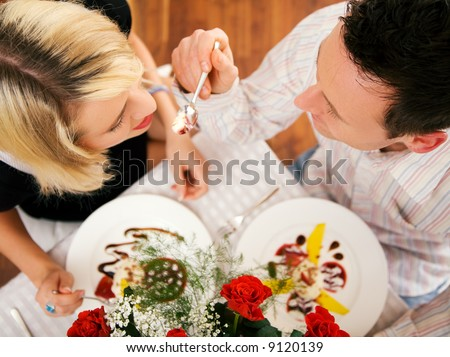Young couple romantic dinner: he is feeding her with desert (yoghurt mousse); focus on faces