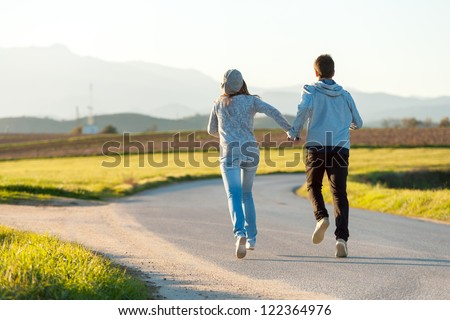 Young couple running along country road.
