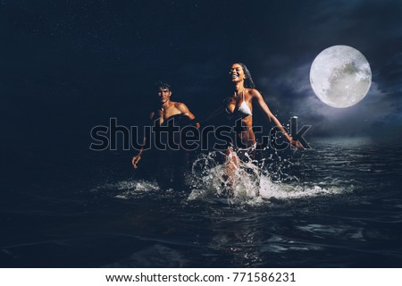 Young couple running in the ocean during the night bath