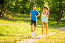 Young couple running in the park on the sunny day