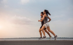 Young couple running on the street be running for exercise. Athletes running fitness to stay healthy. running and lifestyle concept.