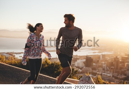 Young couple running together outdoors. Happy young man and woman jogging on country road during sunrise. Two people enjoying morning run.