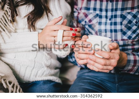 Young couple\'s hands with two cups of hot tea