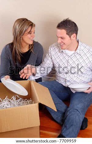 Young Couple Sat On The Floor Unpacking Boxes In Their New Home