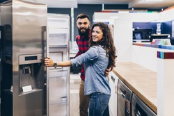 Young couple, satisfied customers choosing fridge in appliances store.