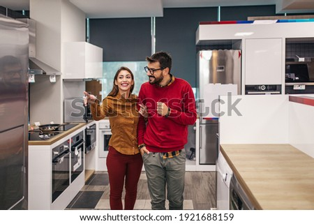 Young couple, satisfied customers choosing fridges in appliances store.