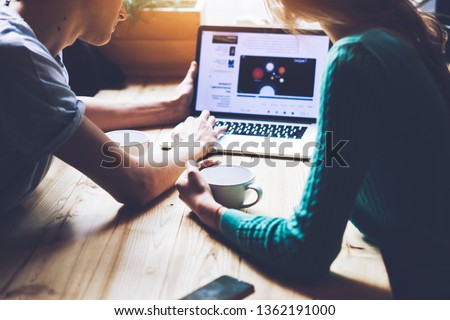 Photo of Young couple searching information for planning future trip togetherness making booking of hotel on website using free 4g internet indoors, man and woman chatting during romantic date in coffee shop