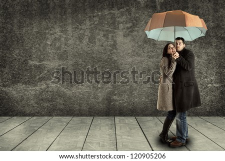 young couple searching protection under an umbrella