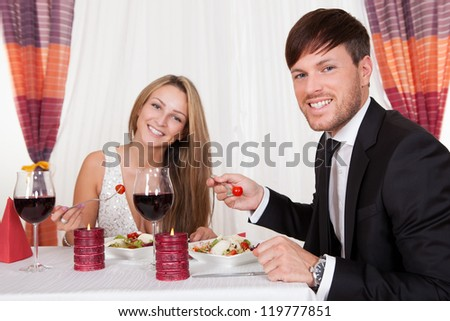 Young couple seated at a restaurant table enjoying a romantic dinner by candlelight and drinking red wine