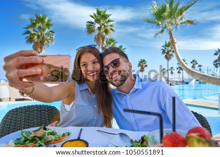 Young couple selfie smartphone photo in a swimming pool restaurant