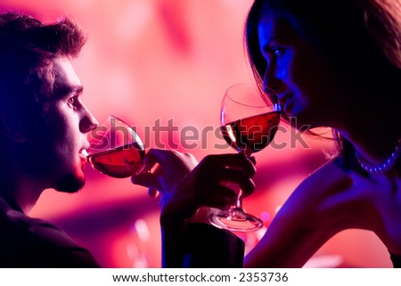 Young couple sharing a glass of red wine in restaurant, celebrating or on romantic date