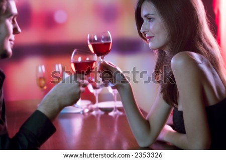 Young couple sharing a glass of red wine in restaurant, celebrating or on romantic date. Focus on woman.