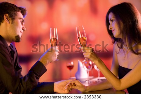 Young couple sharing champagne glasses in restaurant, celebrating or on romantic date