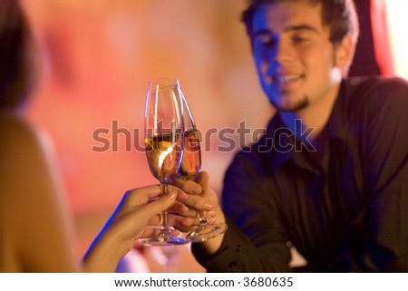 Young couple sharing champagne glasses in restaurant, celebrating or on romantic date. Focus on glasses.