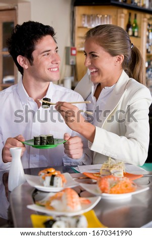 Young couple sharing food in Japanese restaurant using chopsticks