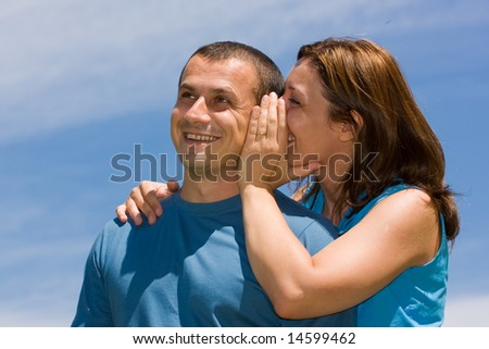 Young couple sharing secrets under blue sky