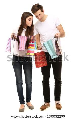 Young couple shopping and holding many shopping bags isolated on white
