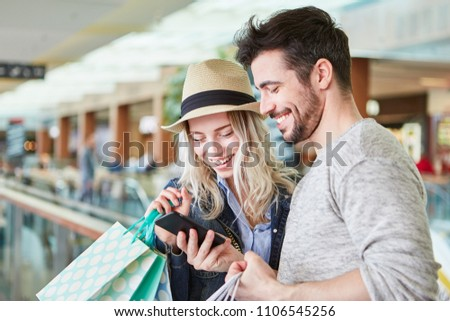 Young couple shopping uses smartphone app for price comparison