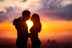 Young couple silhouette hugging and kissing outdoors at sunset background. Sun between them. Man with cowboy hat at his back