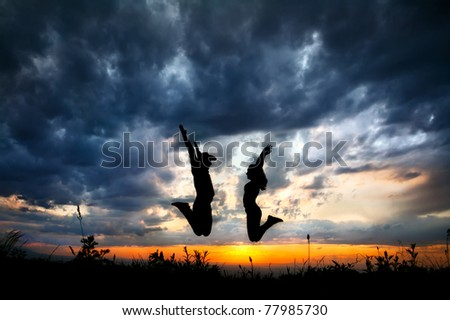 Young couple silhouette jumping outdoors at sunset dramatic sky background. Man in cowboy hat