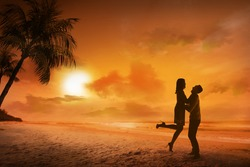 Young couple silhouette on a beach on sunset background