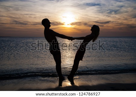 Young couple silhouette  on a sea beach holding hands and looking at sunset under the sea