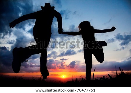 Young couple silhouette running toward the sun outdoors at sunset dramatic sky background. Man in cowboy hat holding hand of woman