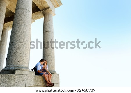 young couple sit at an old monument and enjoy some lunch while exploring on their travels