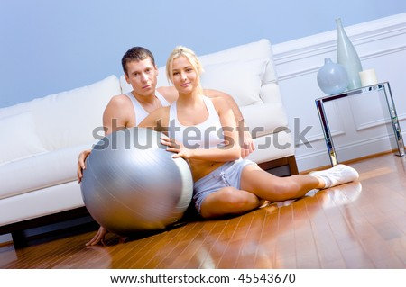 Young couple sit on the wood floor, smiling and holding a silver exercise ball. Horizontal shot.