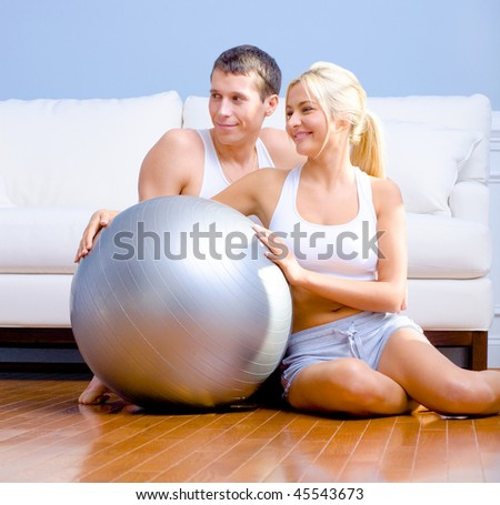 Young couple sit on the wood floor, smiling off to the side while holding a silver exercise ball. Horizontal shot.