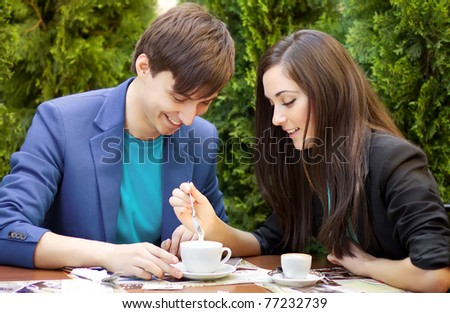 Young couple sitting at a table and drink coffee