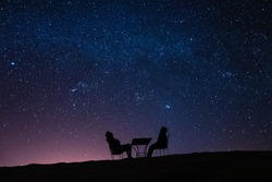 young couple sitting at a table on a desert dune while talking, relaxing and observing the stars and the milky way above them