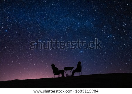young couple sitting at a table on a desert dune while talking, relaxing and observing the stars and the milky way above them Stock photo ©