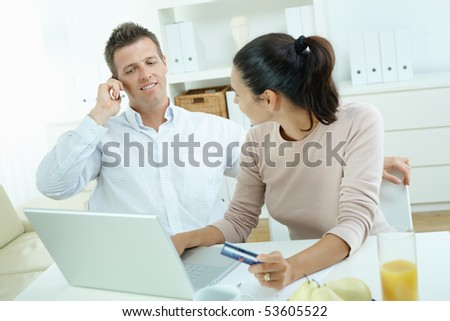 Young couple sitting at desk shopping on internet from home. Calling phone, using laptopcomputer and paying with credit card.