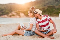 Young couple sitting at the beach and reading a book
