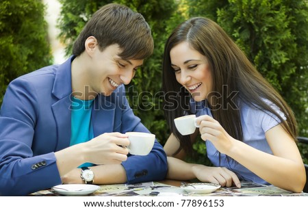 Young couple sitting at the table and drink coffee