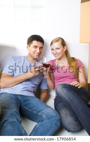 Young couple sitting between cardboard boxes and drinking wine. They're smiling and looking at camera. Front view.