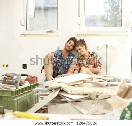 Young couple sitting exhausted in house under construction among construction waste, smiling.