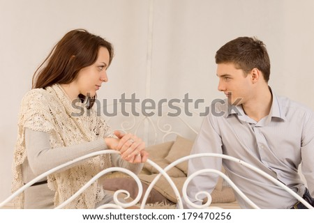 Young couple sitting having a private discussion as they relax on an old wrought iron sofa or bed looking deeply into each others eyes