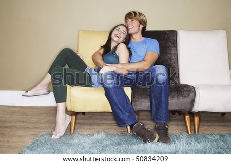 Young couple sitting, hugging, laughing on sofa