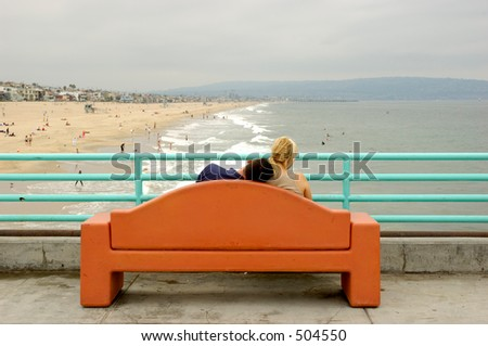 Young couple sitting in a bench over the pier. The boyfriend has his head on his girlfriend's shoulder and she is looking away to the right.